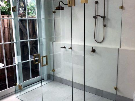 Frameless glass double shower screen with brass hardware
