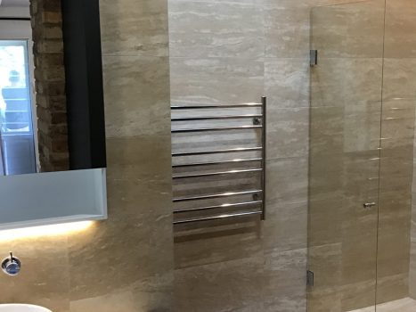 Frameless glass shower screen with polished silver hardware